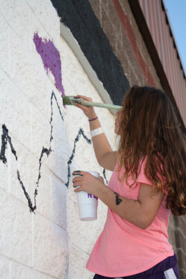 A student from Laurel High works on their mural at the MasterLube in Laurel.